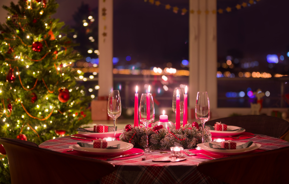 Beautiful decorated table with candles and christmas garlands