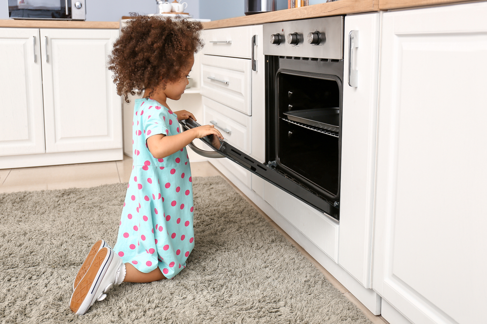 Girl playing with oven kitchen