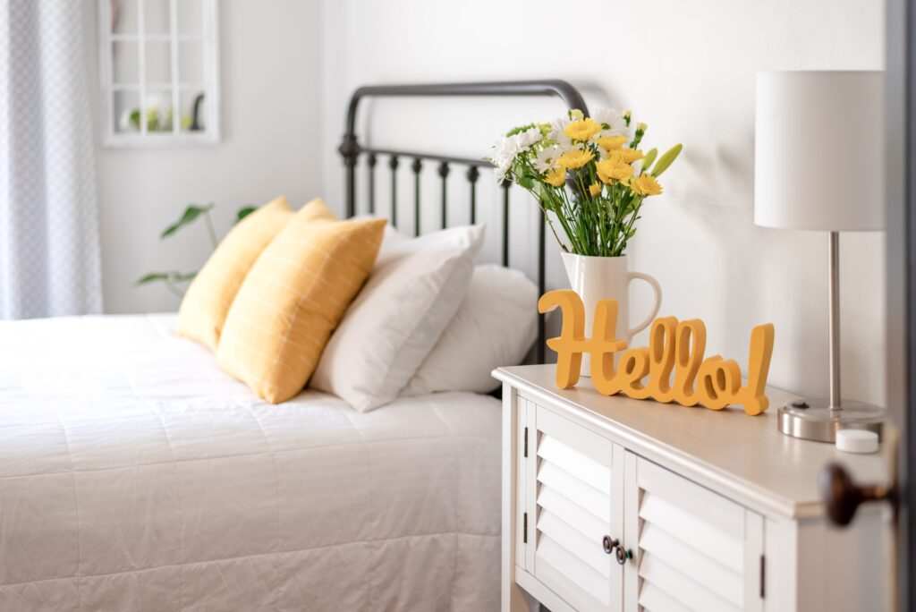 Cheerful yellow hello sign and fresh flowers in a clean and bright guest room